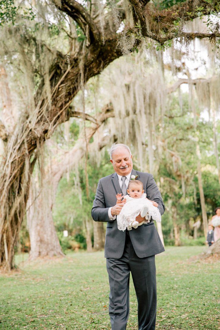 father carrying flower girl